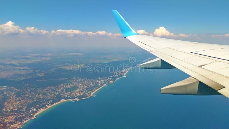 飞机在窗口外面的翼视图在多云天空地球和蓝色海 背景 假日假期背景 翼 免版税图库摄影