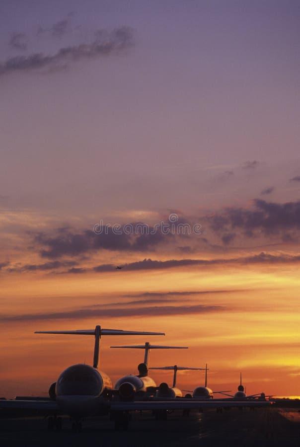 飞机坐柏油碎石地面在日落 库存照片