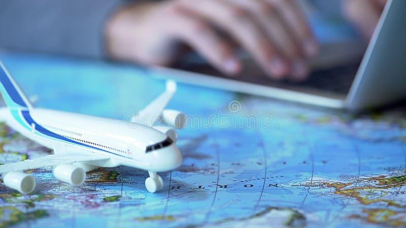 飞机式样特写镜头, defocused人售票飞行在网上在膝上型计算机卖票 库存图片