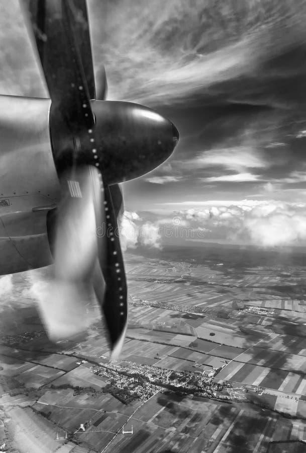飞机推进器在飞行中有托斯坎乡下背景 免版税库存照片