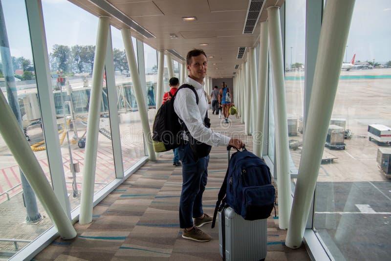 飞机搭乘 运载手提行李袋子的年轻男性乘客,走飞机搭乘走廊 库存照片