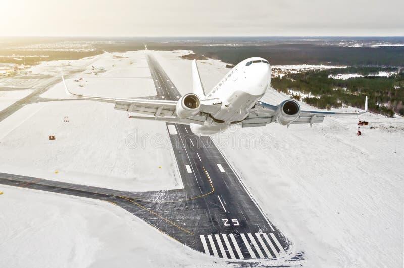 飞机是攀登飞行水平面高视图在天空中,以跑道的冬天机场为背景,城市,雪,前面 免版税库存照片