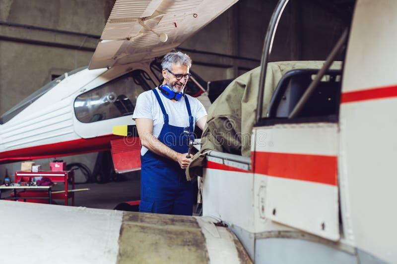 飞机机械员在机场检查并且检查一架喷气机的技术在飞机棚 免版税图库摄影