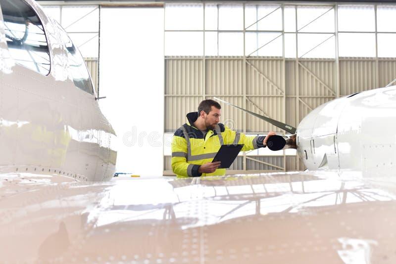 飞机机械员检查并且登记喷气机的技术 免版税库存图片