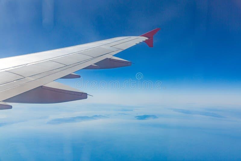 飞机的翼 旅行的概念 在云彩的飞机空运 免版税库存图片