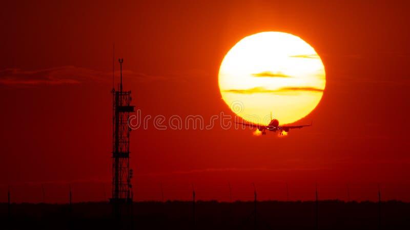 飞机着陆或起飞在日落与红色天空在布加勒斯特国际机场,简单的察觉 免版税库存照片