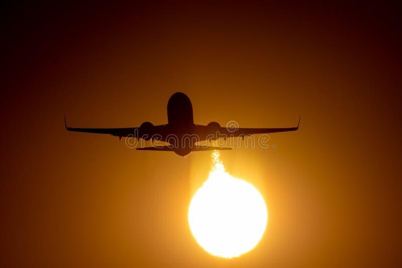 飞机着陆或起飞在日落与红色天空在布加勒斯特国际机场,简单的察觉 图库摄影