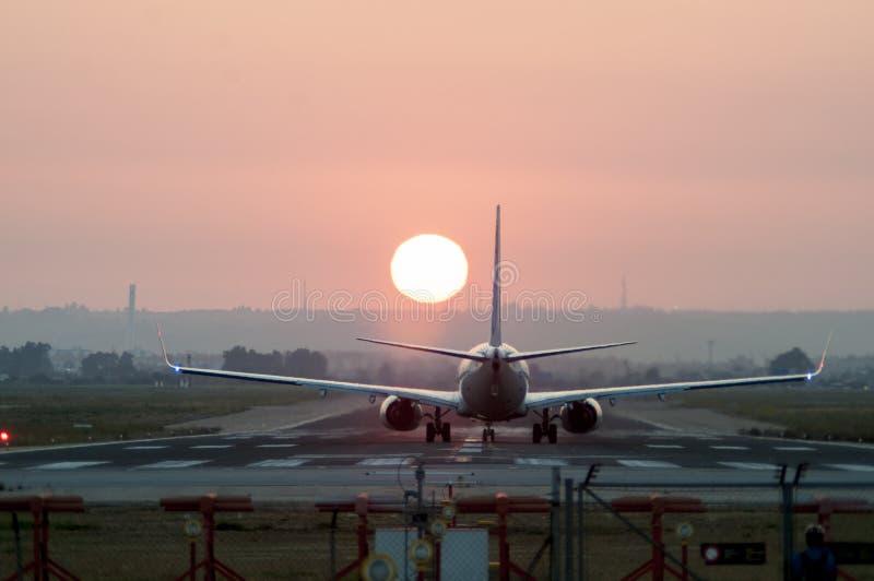 飞机着陆的Iconical图象在日落的一个机场 免版税库存图片
