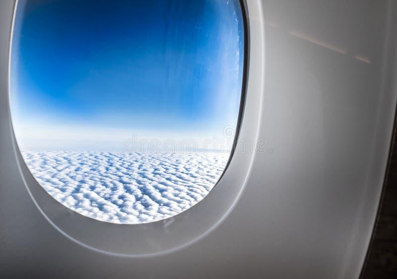 飞机窗口,当飞行进行下去在云彩和蓝天时, Tr 免版税库存图片