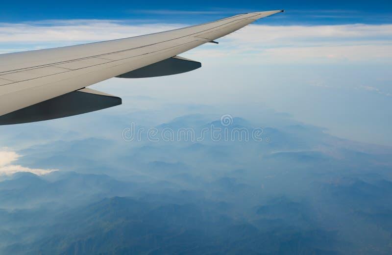 飞机翼在山的 在天空蔚蓝和白色云彩的飞机飞行 r ?? 库存图片