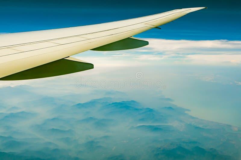 飞机翼在山的 在天空蔚蓝和白色云彩的飞机飞行 r ?? 免版税库存照片