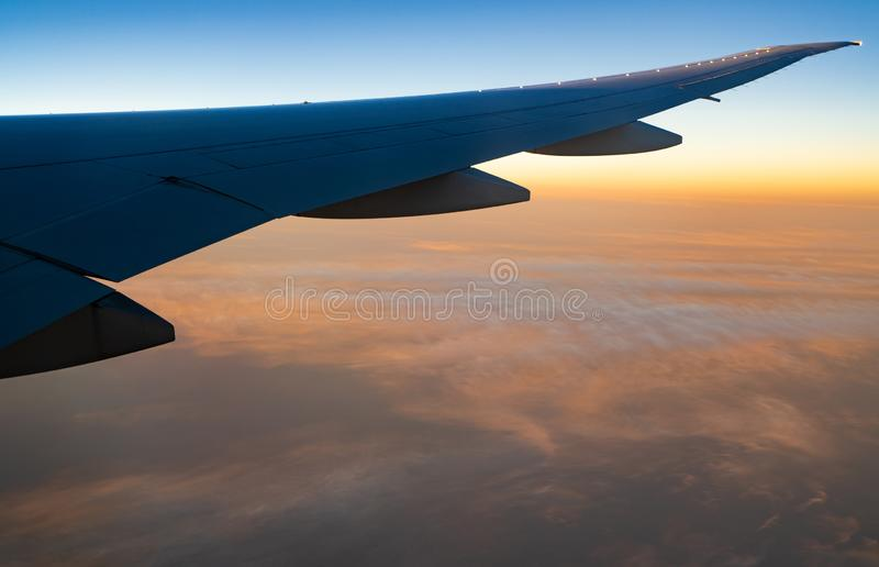 飞机翼在白色云彩的 在日出天空的飞机飞行 r o 免版税库存照片