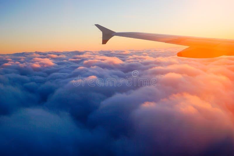 飞机翼在飞行中从窗口,日落天空 免版税库存图片