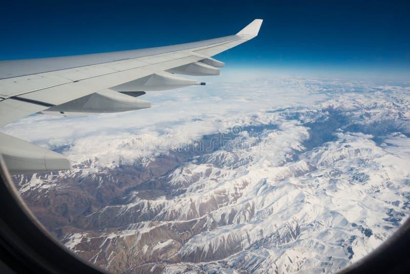 飞机翼看法在雪山的 免版税库存图片