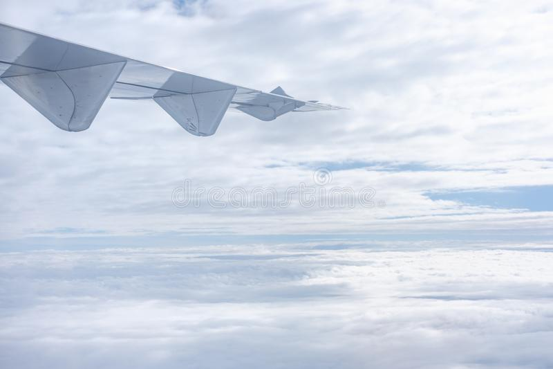 飞机翼,当飞行与多云天空时 运输和tr 库存图片