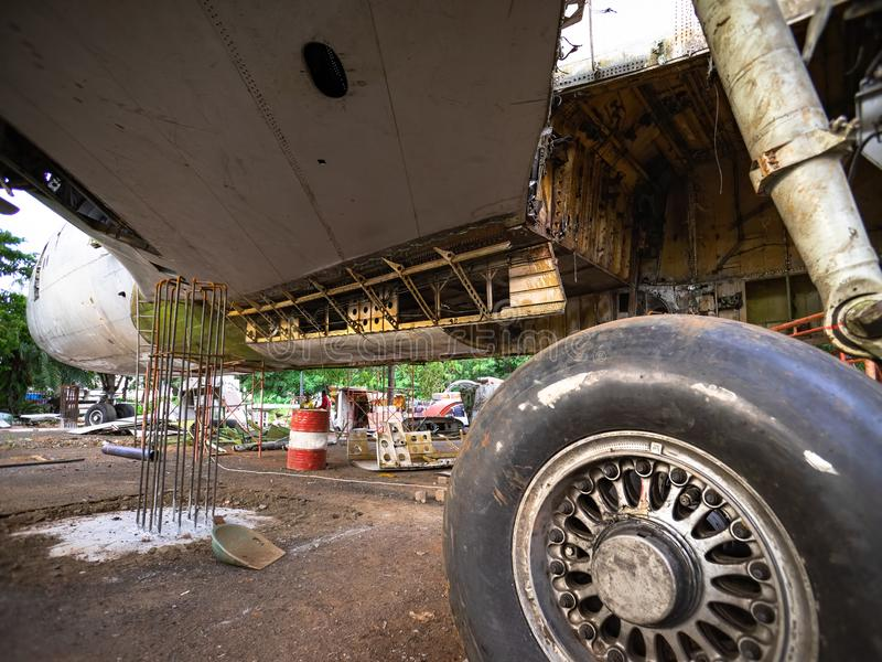 飞机轮胎在老废品旧货栈的修理中 生锈和残破的可撤回的水力被管理的飞机轮子 图库摄影