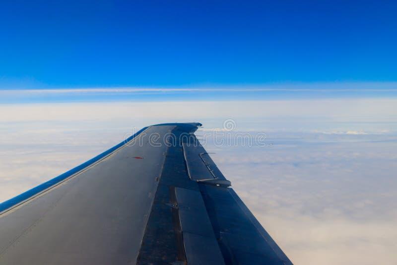 飞机飞行翼在云彩上的在蓝天 免版税库存照片