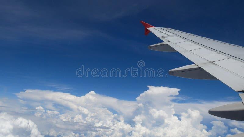 飞机飞行 一次飞机飞行的翼在白色云彩和蓝天上的 从窗口的美好的鸟瞰图 免版税库存照片