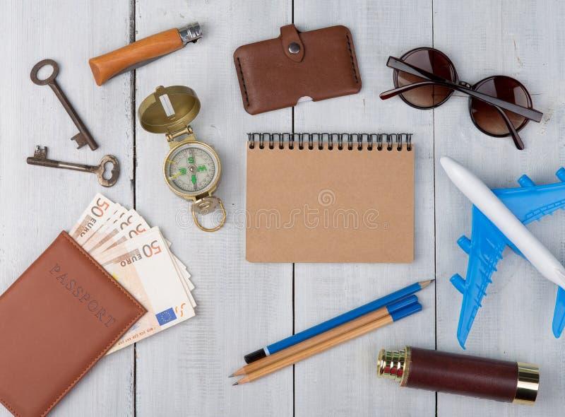飞机,护照,金钱,指南针,太阳镜,双筒望远镜,笔记本,钥匙,钱包 免版税图库摄影