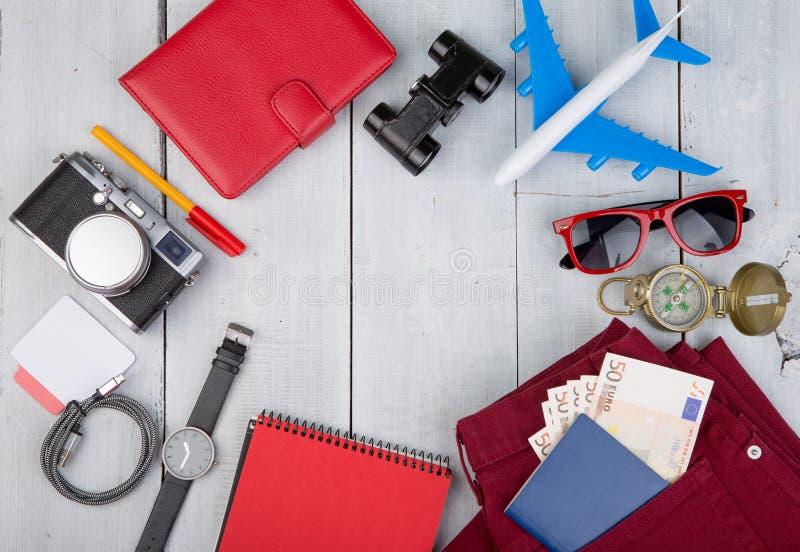 飞机,护照,金钱,照相机,指南针,太阳镜,双筒望远镜,牛仔裤,手表,笔记薄,钱包 库存照片