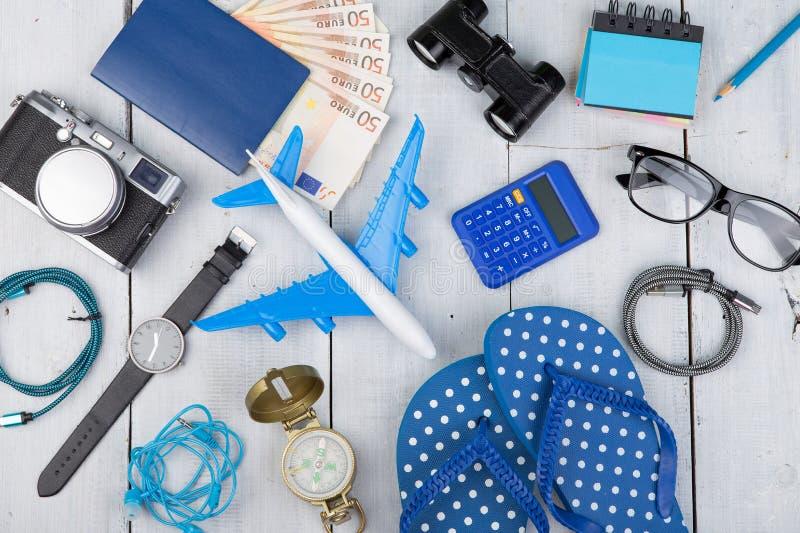 飞机,护照,金钱,照相机,指南针,笔记本,双筒望远镜,手表,在白色木桌上的触发器 免版税库存图片