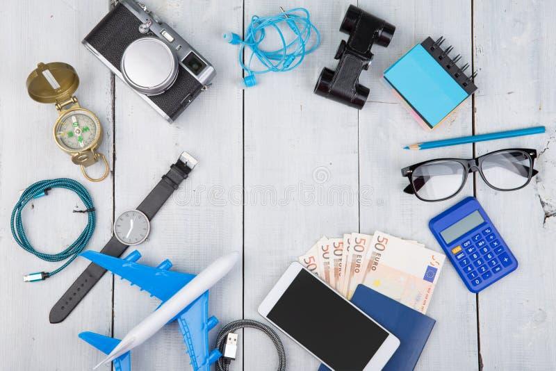 飞机,护照,金钱,照相机,指南针,耳机,双筒望远镜,手表,智能手机,计算器,玻璃 图库摄影