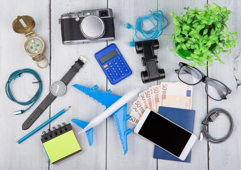 飞机,护照,金钱,照相机,指南针,耳机,双筒望远镜,手表,智能手机,计算器,玻璃 免版税库存照片