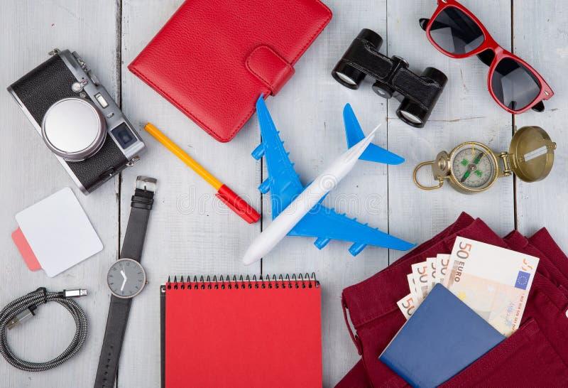 飞机,护照,金钱,照相机,指南针,耳机,太阳镜,双筒望远镜,牛仔裤,笔记薄,钱包 库存照片