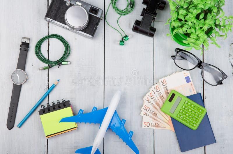 飞机,护照,金钱,照相机,耳机,双筒望远镜,手表,计算器,在白色木桌上的镜片 库存照片