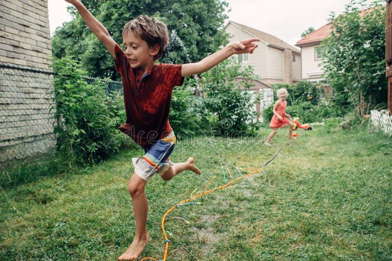 飞溅与水管喷水隆头的儿童孩子在后院在夏日 库存照片
