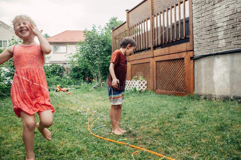 飞溅与水管喷水隆头的儿童孩子在后院在夏日 免版税库存照片