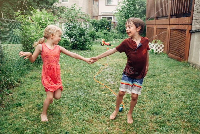 飞溅与水管喷水隆头的儿童孩子在后院在夏日 库存图片