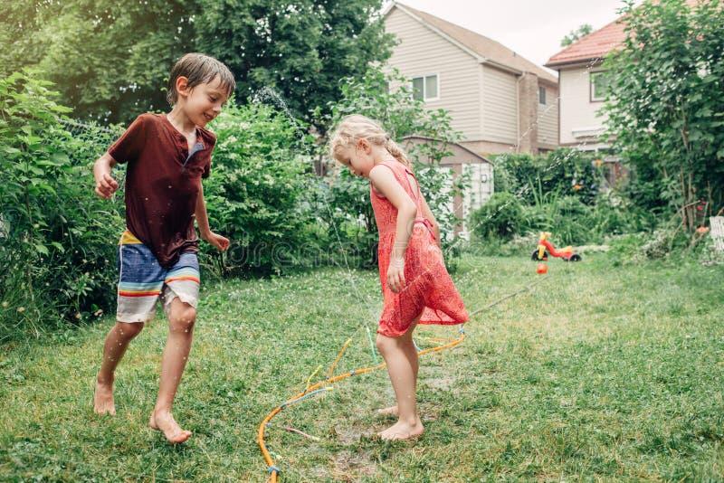 飞溅与水管喷水隆头的儿童孩子在后院在夏日 免版税库存图片