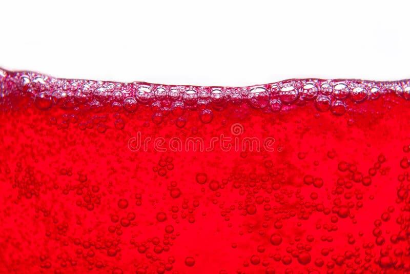 飞溅与泡影和紧密露点的红色苏打水  免版税图库摄影