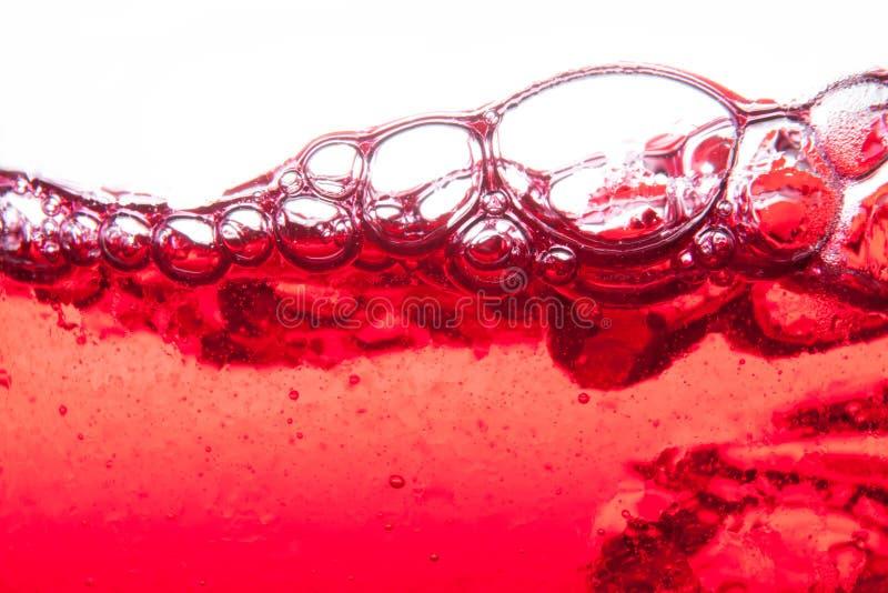 飞溅与泡影和紧密露点的红色苏打水  免版税库存照片
