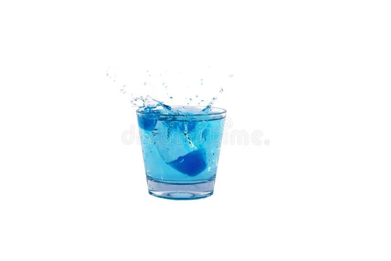 飞溅入杯的蓝色冰块水 免版税库存图片