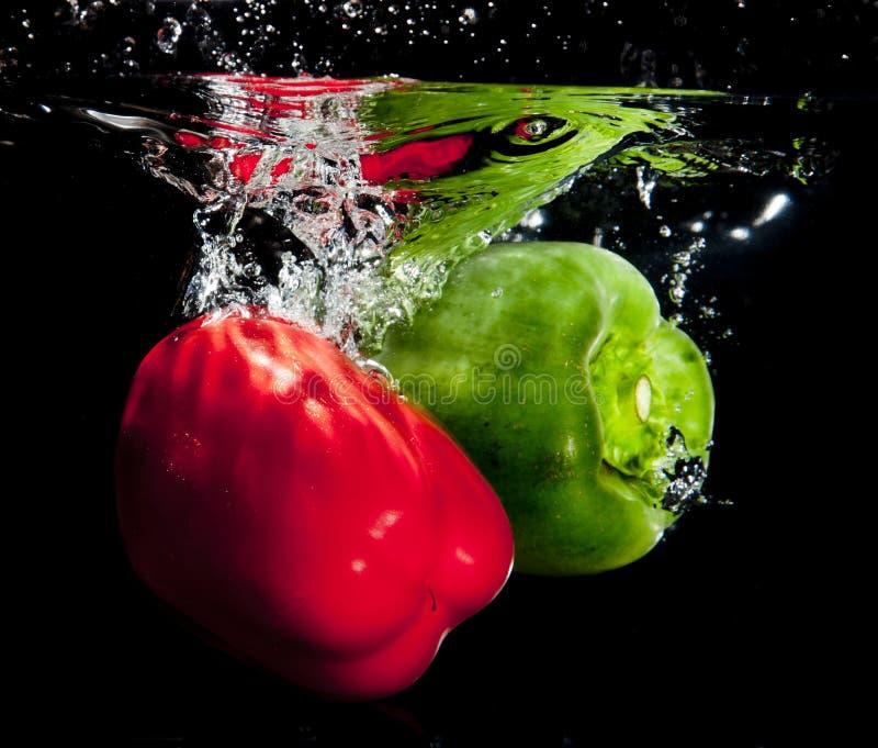 飞溅入水的胡椒 库存图片