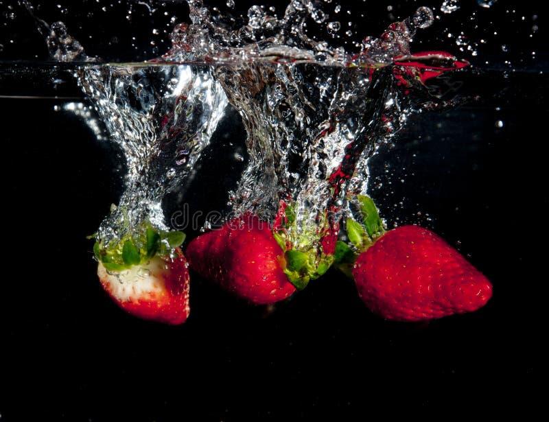 飞溅入水的草莓 库存照片