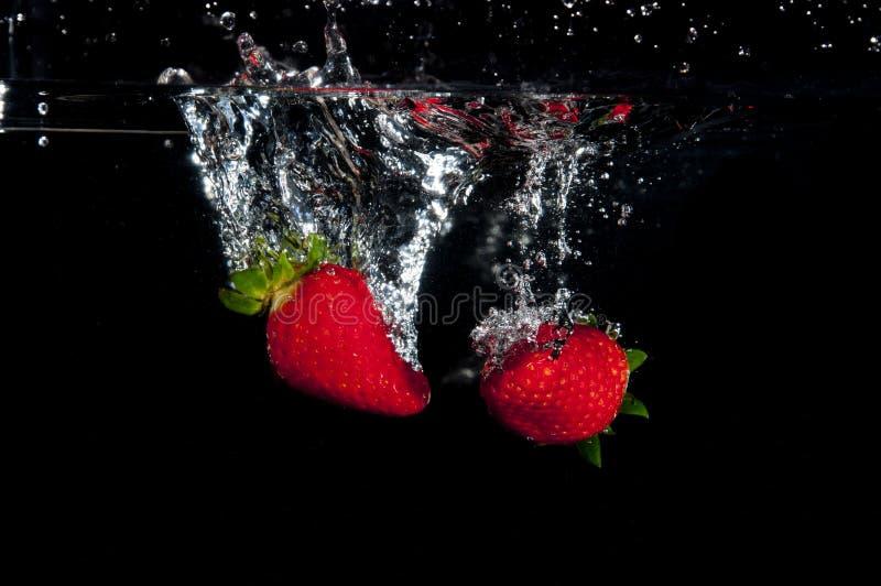 飞溅入水的草莓 免版税图库摄影