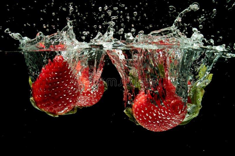 飞溅到水的草莓 图库摄影
