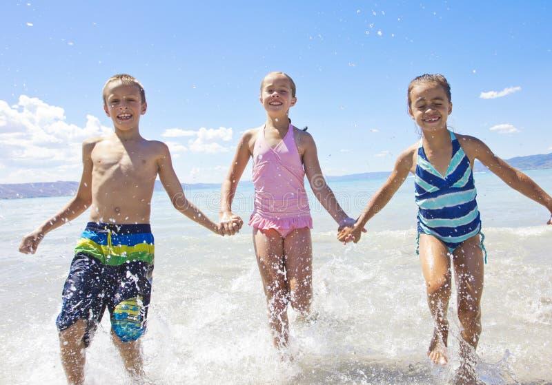 飞溅和使用在海洋的孩子 免版税库存照片