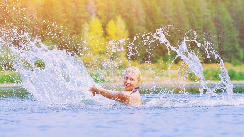 飞溅喷水消散的活跃年轻快乐的白肤金发的妇女在河 美丽的健康夫人放松和笑 免版税库存照片