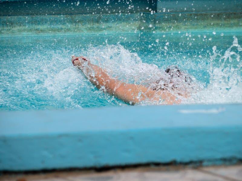 飞溅在一蓝色游泳场的游泳者水 库存照片