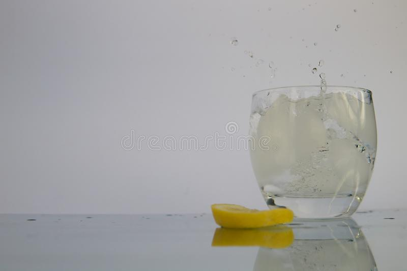 飞溅在冰水的柠檬切片 免版税库存照片