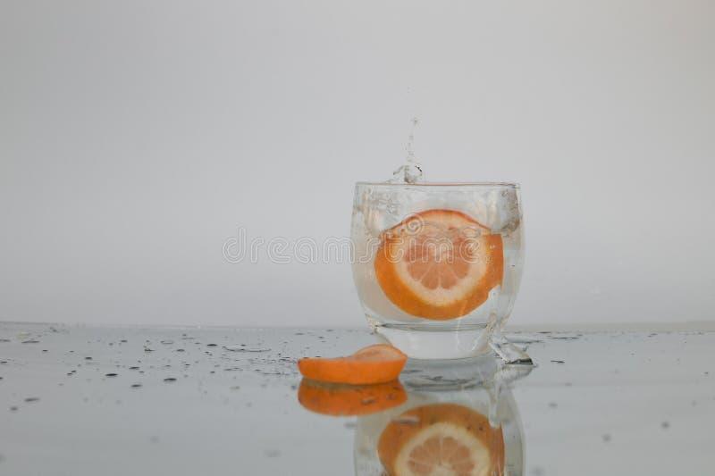 飞溅在冰水的葡萄柚 免版税库存照片