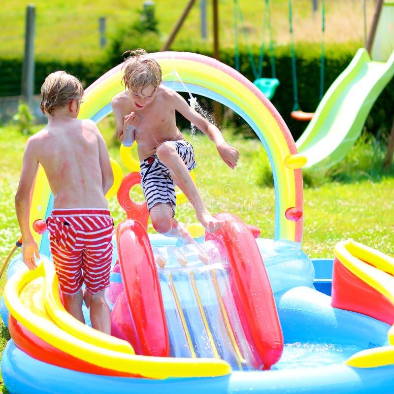 飞溅在可膨胀的庭院水池的愉快的孩子 库存照片