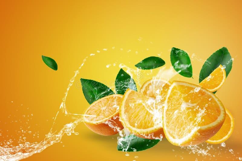 飞溅在新鲜的切的桔子和橙色果子的水在橙色背景 库存图片