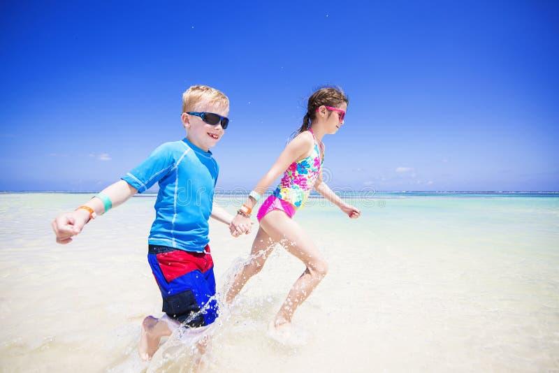 飞溅在海洋的孩子在一个热带海滩假期 免版税库存照片