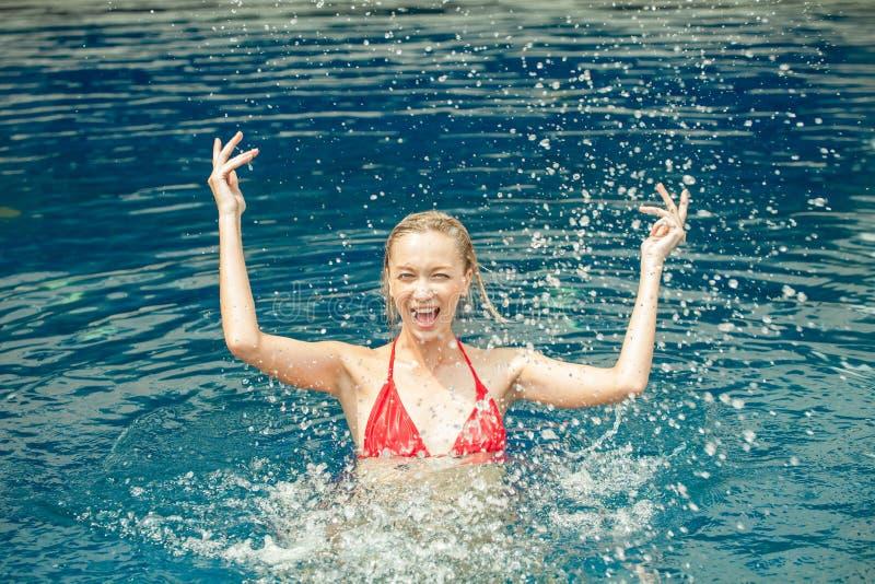 飞溅在游泳池,夫人的美丽的愉快的妇女水  免版税库存照片