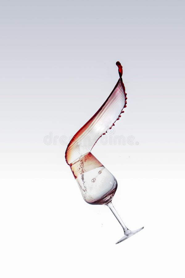飞溅在玻璃外面的红酒,被隔绝在白色背景 免版税库存图片
